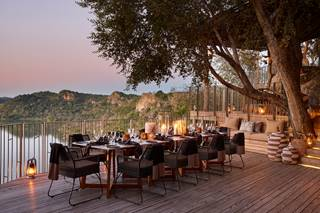 Singita Pamushana Lodge - Dinner table on deck overlooking dam.jpg