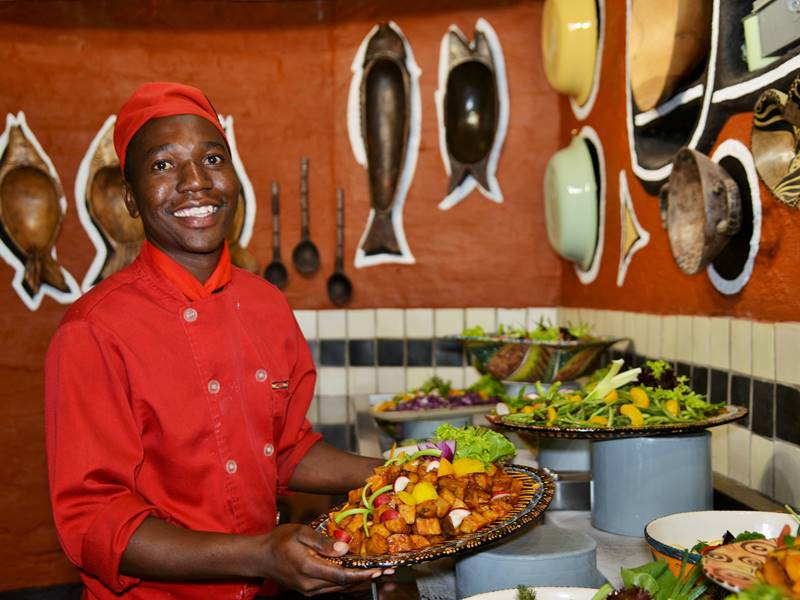 Image 1 - Boma - Dinner & Drum Show chef Tendai Mutava at the salad bar with the new decor in the background.jpg